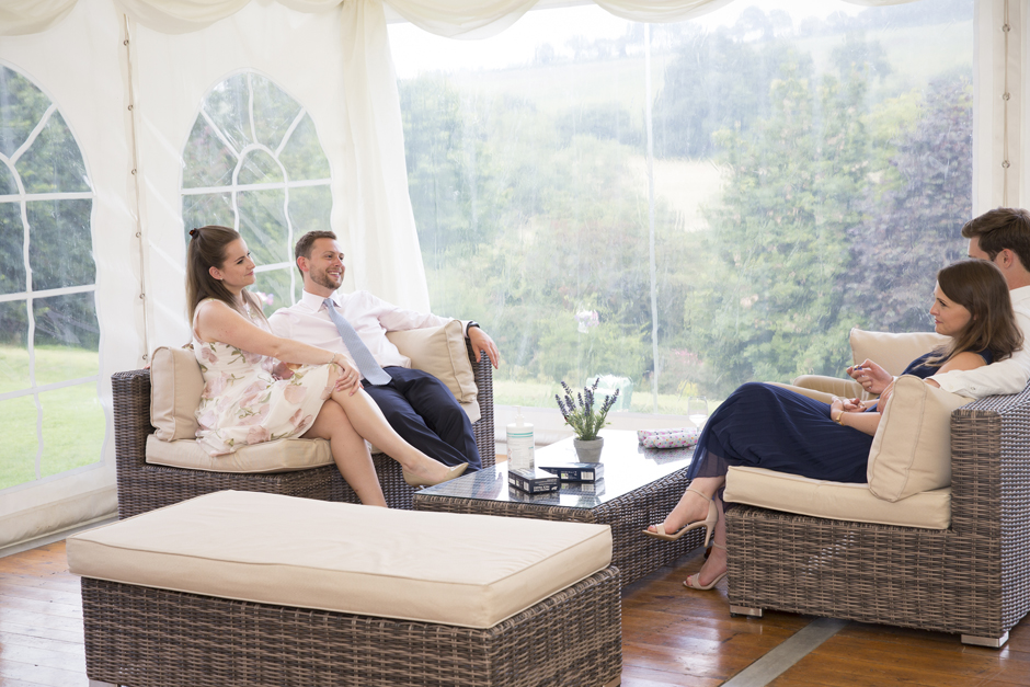 Wedding guests sitting on rattan furniture in marquee overlooking Kent countryside. Captured at Nettlestead Place in Maidstone, Kent.