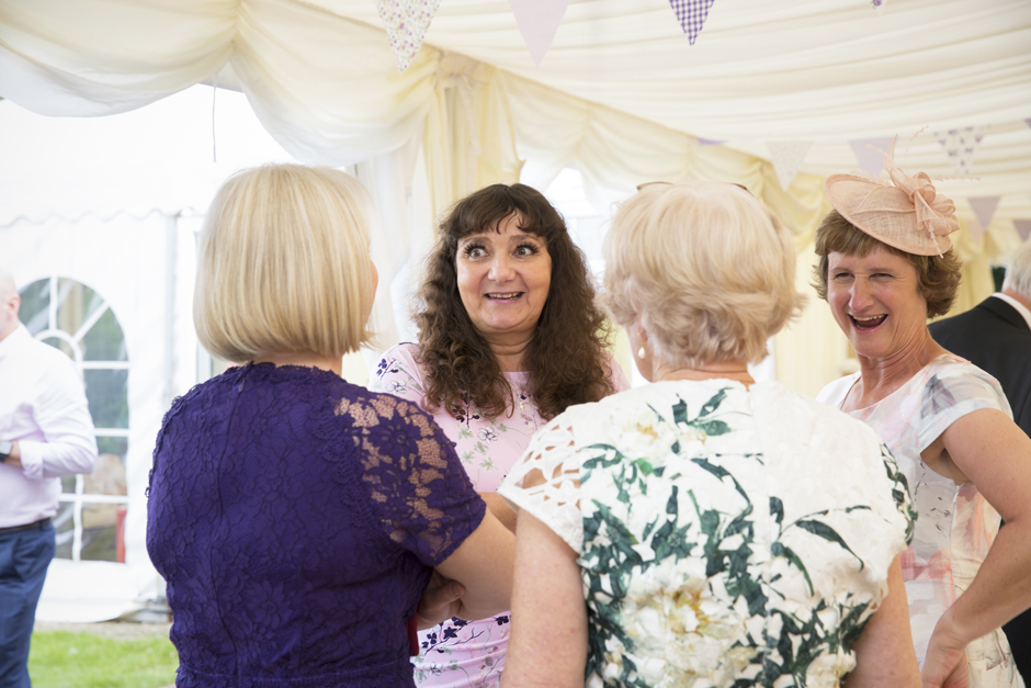 Female wedding guests laughing in marquee at Nettlestead Place in Kent.