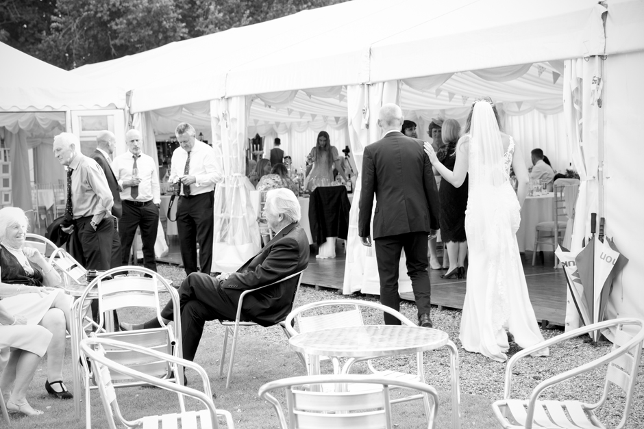 Back of bride and groom as they approach the wedding marquee at Nettlestead Place in Kent.