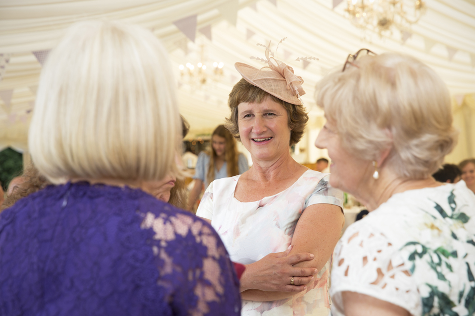 Mother of the bride absorbed in conversation with other wedding guests at Nettlestead Place wedding in Kent.