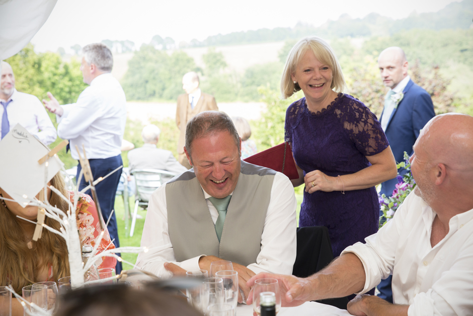 Wedding guests laughing at Nettlestead Place in Maidstone, Kent.