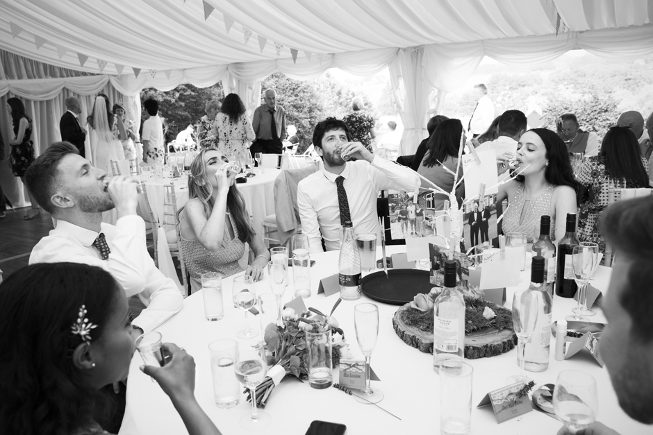 Wedding guests doing tequila shots at the table during evening wedding ceremony at Nettlestead Place, in Kent.