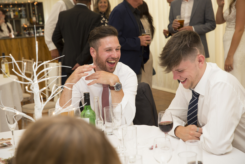 Male wedding guests laughing at a table during evening wedding reception at Nettlestead Place in Kent.
