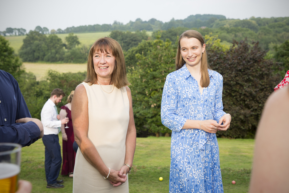 Female wedding guests smiling outside at Nettlestead Place in Kent.