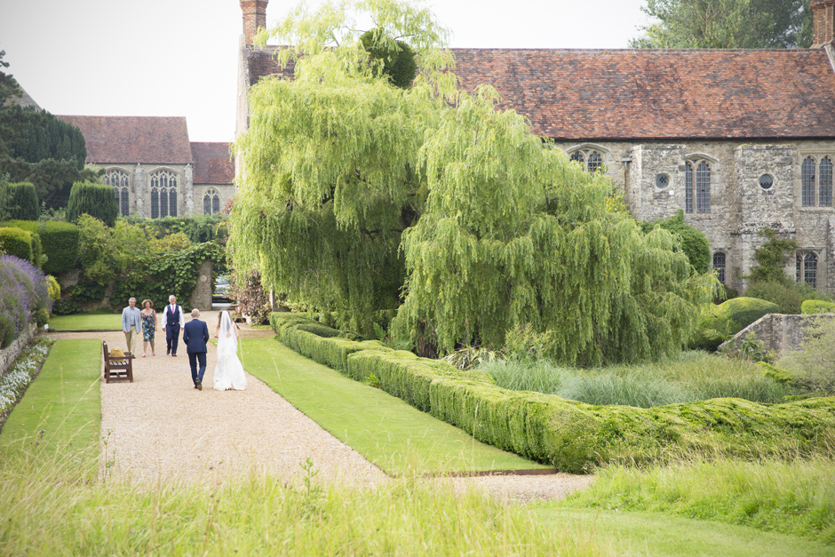 Nettlestead Place house with back of bride and groom walking to greet wedding guests.