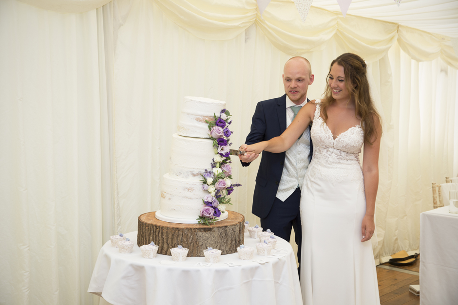 Bride and groom cutting 3-tier wedding cake at Nettlestead Place in Kent.