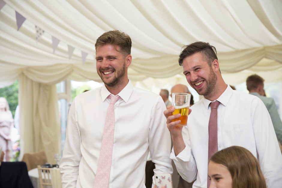 Male wedding guests laughing in marquee at Nettlestead Place in Kent.