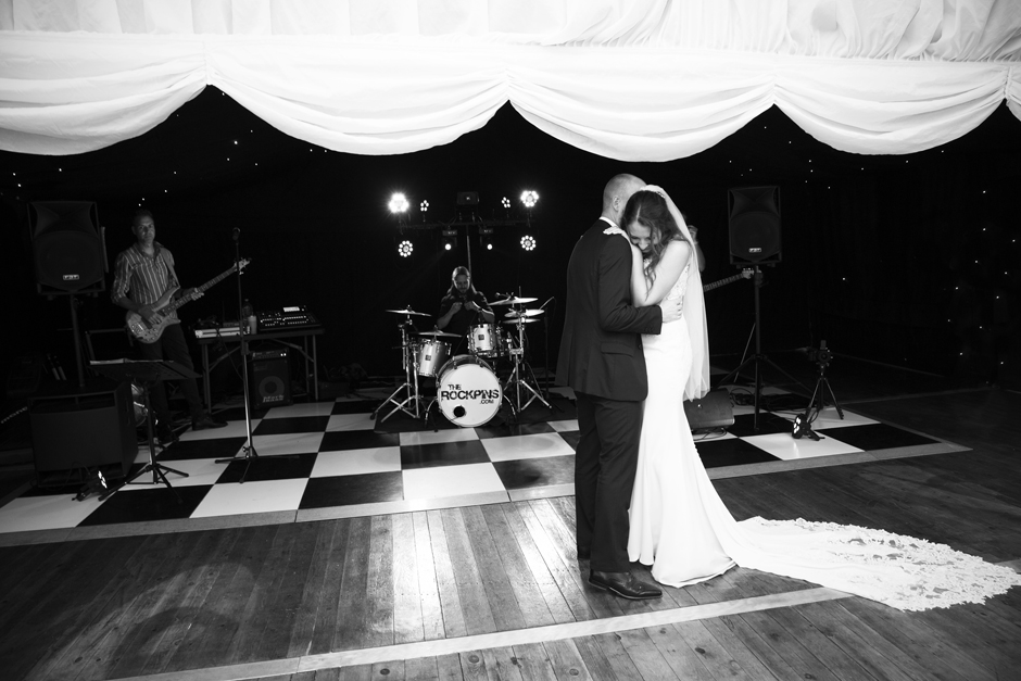 Bride and groom in tight embrace during first dance at Nettlestead Place wedding in Kent. Captured by wedding photographer Victoria Green.